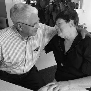 Kuvassa puusepänliike Taitopuun emeritusyrittäjät Simo ja Vuokko Vesamäki puolihalaavat, katsovat toisiaan silmiin, hymyilevät ja salaisuutena kerrottakoon; salamavalon sammuttua suutelevat !